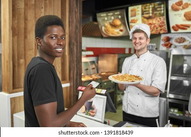 Male client looking at camera and smiling while buying delicious pizza in cafe. African boy standing near cashbox and paying with credit card for junk dood in pizzeria. Concept of fast food and lunch.