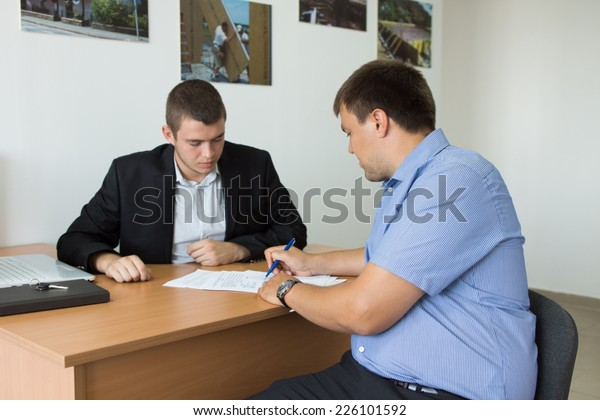 Male Client Signing Written Document on Wooden Desk of Young Real Estate Agent Inside the Firm.