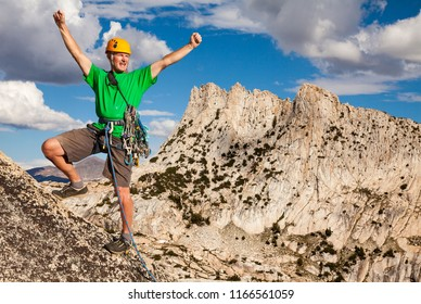 Male climber celebrates on the summit.