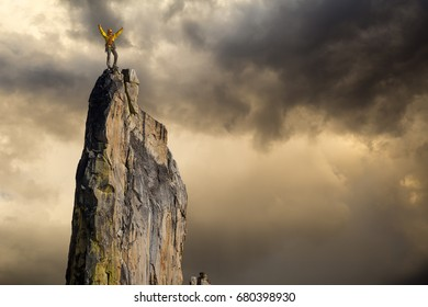 Male climber celebrates on the summit of a sheer rock spire.