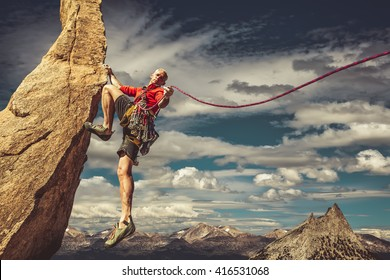 Male climber dangles from a sheer rock spire.