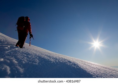 A male climber , dressed in red, climbs down a snowy slope. Winter clear sky day.