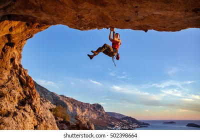 Male climber gripping on handhold while climbing in cave. Rock climbing without rope.