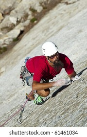 Male climber grips and scampers up a sheer rock wall in Yosemite's high Sierra Nevada mountains.