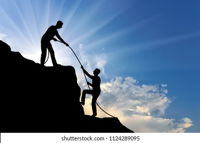 A male climber helps to climb the top of another person by throwing him a rope. Conceptual Scene