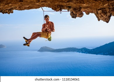 Male climber on overhanging rock arch, beautiful view of coast below. Outdoor active lifestyle.
