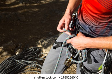 A male climber ties a safety knot eight on the harness before climbing the track. Climbing equipment: rope, quickdraw, safety device, harness. Sports mountain tourism, active lifestyle, extreme sports