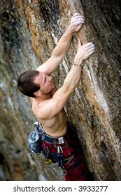 A male climber, viewed from above, climbs a very high and steep crag.