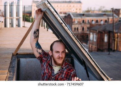Male climbing on roof. Creative leisure time. Romantic date night, young stylish hipster in focus on foreground, dangerous parkour subculture, urban concept