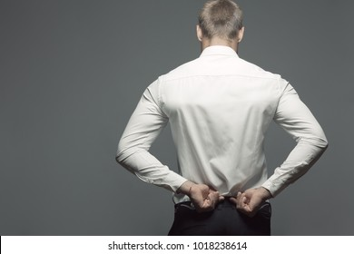 Male clothing concept. Back of young man with great figure undressing, posing over gray background. Copy-space. Studio shot