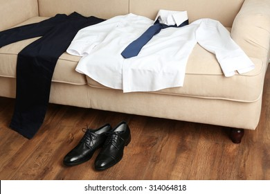 Male clothing on sofa near shoes on floor in room