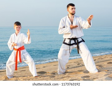 Male coach and boy in karate uniform doing exercises at sunny seaside