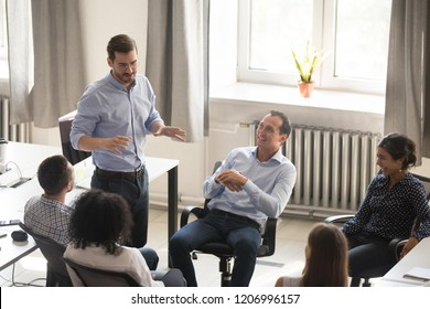 Male coach mentor teacher talking to workers interns, leader teaching friendly happy team in office, project manager speaking about new idea to colleagues at diverse group meeting, corporate training