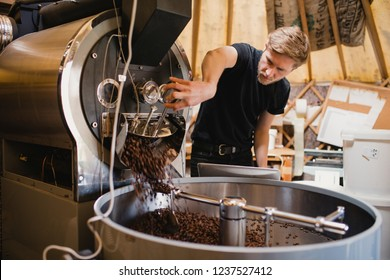 Male coffee shop employee using a coffee bean roasting machine and turning a dial to release the coffee beans.
