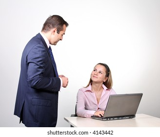 A male colleague offering a suggestion to a female coworker.