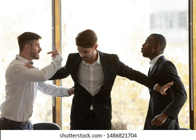 Male colleague set apart angry diverse business men coworkers argue fighting at corporate office meeting, mad employees quarreling shouting having conflict at work, racial hatred harassment concept