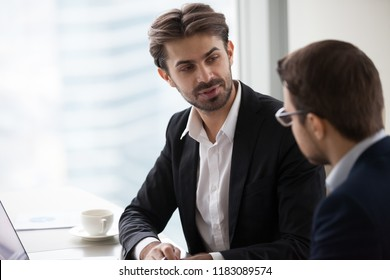 Male colleagues talking in office discussing startup project, focused businessman discuss business idea with partner, serious company CEO explaining or presenting statistics to corporate client