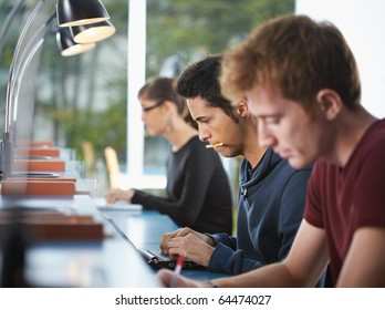 male college student sitting in library, typing on laptop computer. Horizontal shape, side view, waist up