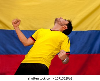 Male Colombian soccer fan celebrating with the Colombian flag in the back