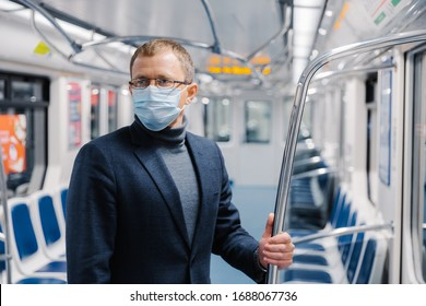 Male commuter poses in empty subway carriage, wears medical mask to prevent infected coronavirus at public metro station, looks somewhere, thinks about social distancing. Disease prevention.