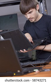 male computer technician installing new software on laptop