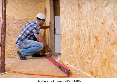 Male Construction Worker Builder Wearing White Hard Hat Measuring Door Frame with Tape Measure Inside Unfinished Home with Exposed Particle Plywood Boards