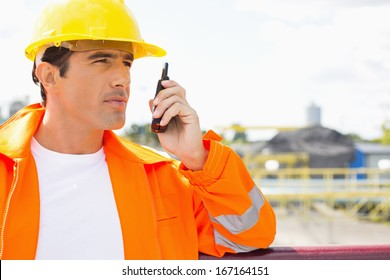 Male construction worker communicating on two way radio at site