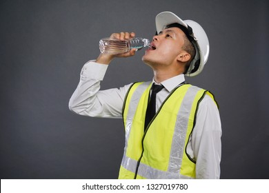 Male construction worker drinking a plain water stair against grey background.