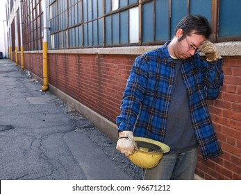 Male Construction Worker, forlorn, outdoors, out of work in alley