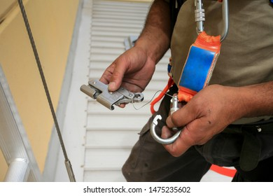 Male construction worker hand demonstration how to clipping industrial Karabiner connected with fall arrest shock absorbing safety lanyard device into stainless back up safety device vertical line