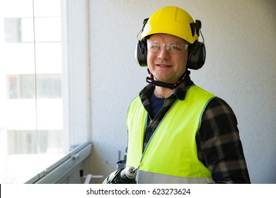 Male construction worker in hard hat with a drill and smiling at the camera. Building and renovation.