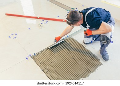 A male construction worker installs a large ceramic tile