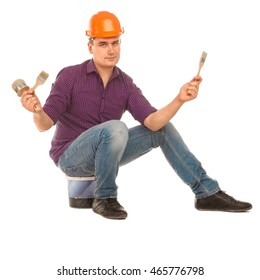 male construction worker sitting on a bucket and holding various brushes in his hand isolated on white background