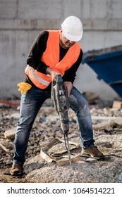 Male construction worker using a jackhammer on construction site