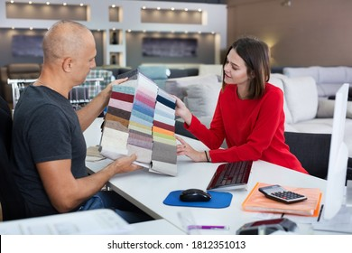 Male consultant helping young woman choosing upholstery fabric in furniture shop. Focus on woman