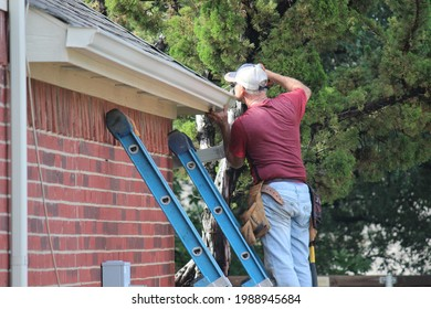 Male contractor installing a gutter system on a two-story residential house in North Texas