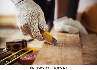 Male contractor working with wooden plank and cutter on the floor. Close-up of mature craftsman's hands in protective gloves with building tools.