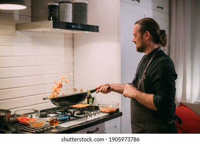 A male cook is cooking at the stove at home in the kitchen. A young guy in an apron in the kitchen at the gas stove fries food in a wok