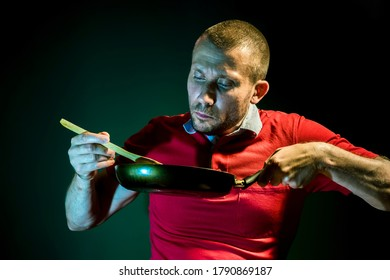 Male cook cooks in a frying pan on a dark green background