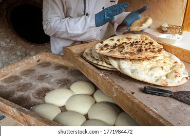A male cook makes tortillas. The preparation of bread. The process of baking bread in a traditional Georgian stove - tone, tandoor.