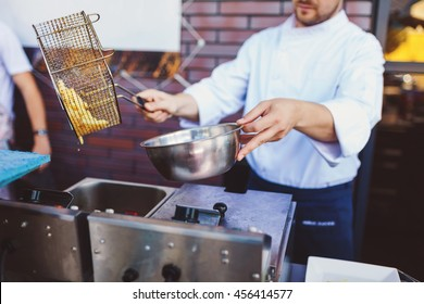 Male cook preparing delicious French fries at street cafe