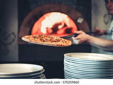 male cook pulls out the finished pizza from the stone oven with fire