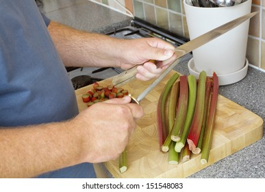 Male cook sharpening knife on a steel in a domestic kitchen. There is rhubarb on the chopping board.