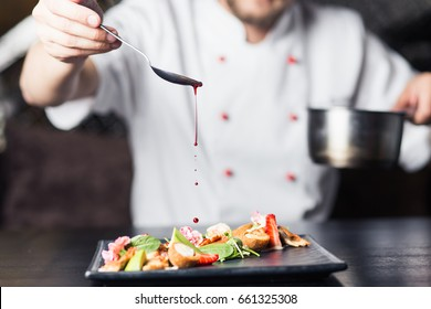 male cooks preparing meat in the restaurant kitchen