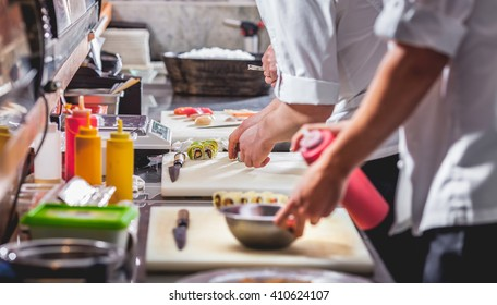 male cooks preparing sushi in restaurant kitchen