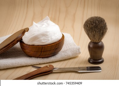 Male cosmetic products and supplies used by men to shave concept with a straight razor, towel, shaving brush and foam on wood background