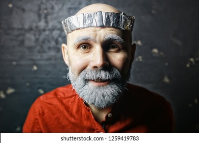 male cosplay king in a crown with a beard / portrait of a hipster with a gray beard, cosplay in vintage style