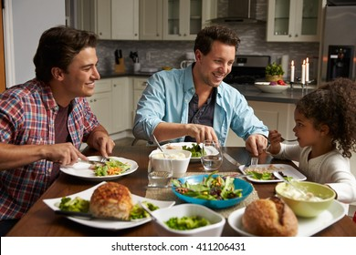 Male couple and black daughter dining in their kitchen