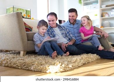 male couple sitting on the floor of their front room with their children, helping them do their homework