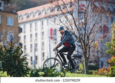 Male courier with electric bicycle delivering packages in city.
